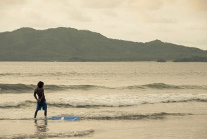 A surfer at sunset at Tamarindo beach, Costa Rica