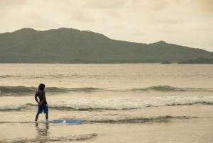 A surfer at sunset at Tamarindo beach, Costa Rica
